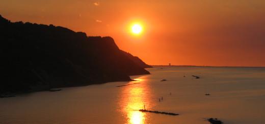 Suggestivo riflesso sul mare del sole al tramonto in Baia