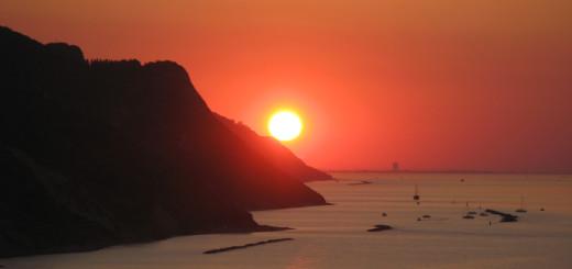 Il sole al tramonto sfiora il Monte San Bartolo