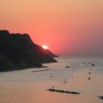 La sera del 20 luglio 2016 il sole tramonta dietro il San Bartolo