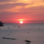 Il sole tocca Rimini all'orizzonte al tramonto la sera del 29 giugno 2016