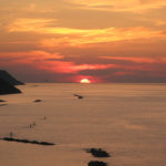 Il sole scompare dietro Rimini durante il tramonto del 6 giugno 2016
