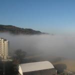 La nebbia copre la spiaggia e i primi palazzi in Baia