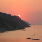 Al tramonto il sole si nasconde dietro il San Bartolo.