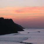 Il rosso crepuscolo in Baia Flaminia, con le prime luci notturne su Rimini