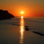 Il sole al tramonto crea una striscia infuocata sul mare