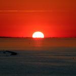 Il contatto tra il sole ed il mare su sfondo infuocato