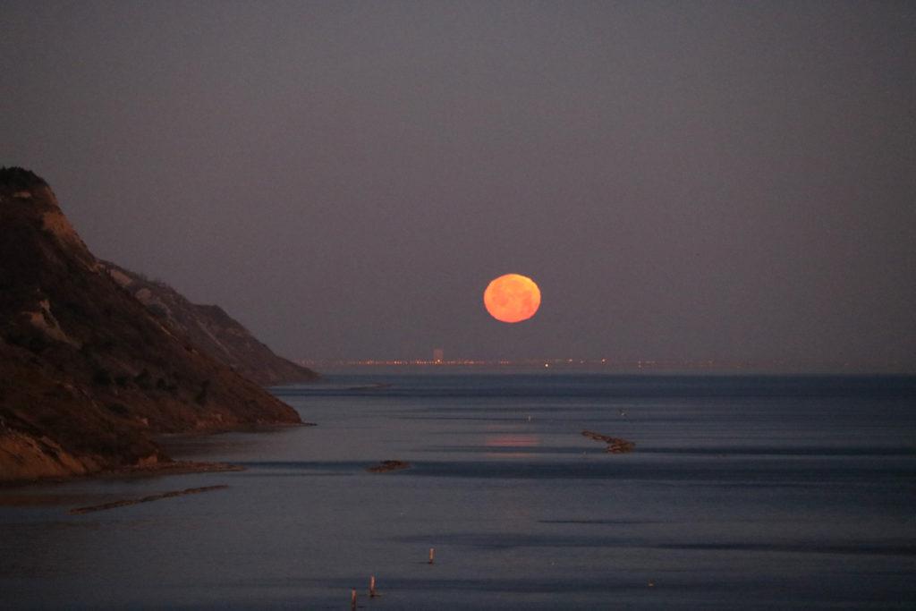 Luna al tramonto sul mare in Baia Flaminia